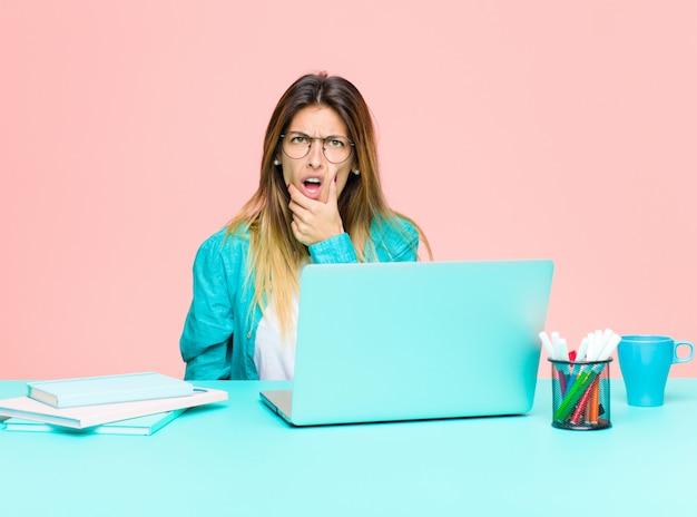 Die junge hübsche frau, die mit einem laptop mit dem mund und augen weit arbeitet, öffnen sich