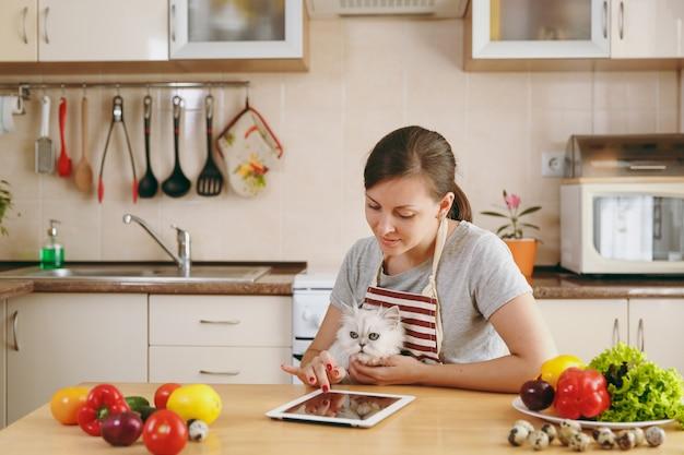 Die junge hübsche frau mit weißer perserkatze in der küche mit tablet auf dem tisch. gemüsesalat. diätkonzept. gesunder lebensstil. kochen zu hause. essen zubereiten.