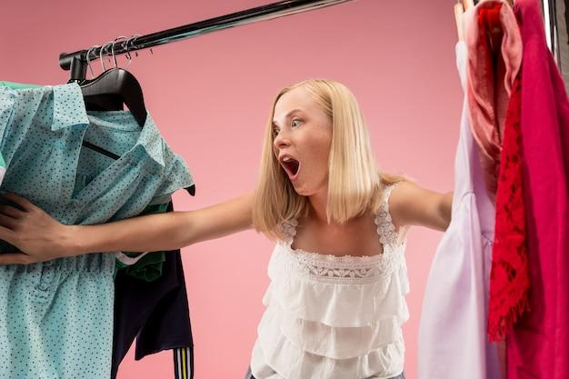 Die junge hübsche frau schaut sich kleider an und probiert sie an, während sie im laden wählt