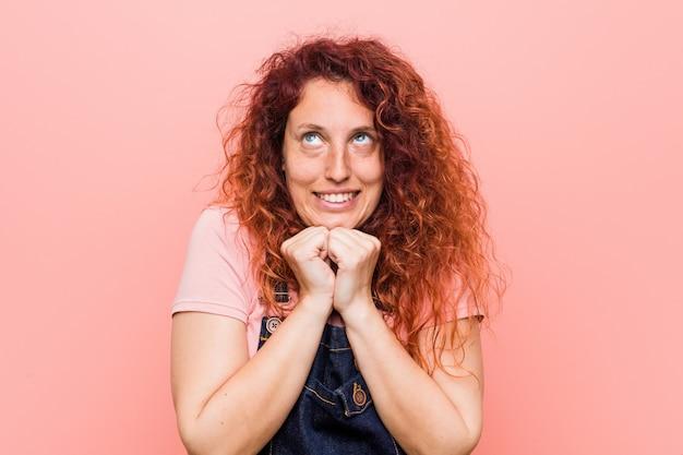 Die junge hübsche ingwer-rothaarigefrau, die einen jeanslatzhose trägt, hält hände unter kinn, schaut glücklich beiseite.