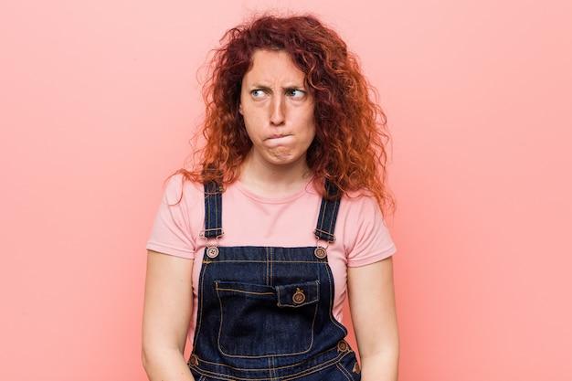 Die junge hübsche ingwer-rothaarigefrau, die einen verwirrten jeanslatzhose trägt, fühlt sich zweifelhaft und unsicher.
