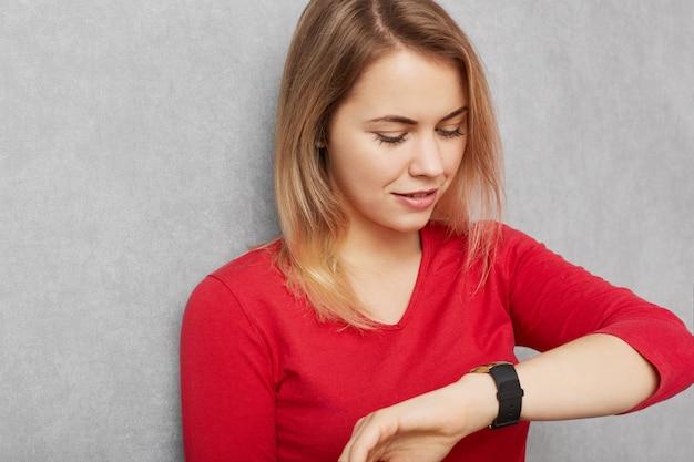 Die junge hübsche junge frau überprüft die zeit auf der armbanduhr, hat es eilig oder kommt zu spät zum treffen, wartet auf jemanden, der es satt hat zu warten, isoliert über der grauen wand. personen, zeit, terminkonzept