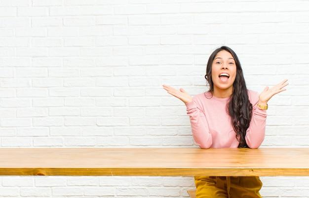 Die junge hübsche lateinische frau, die glücklich und aufgeregt, entsetzt mit einer unerwarteten überraschung mit beiden händen schaut, öffnen sich nahe bei dem gesicht, das vor einer tabelle sitzt