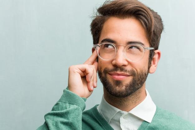 Die junge hübsche unternehmermann-gesichtsnahaufnahme, die oben verwirrt über eine idee denkt und schaut, würde versuchen, eine lösung zu finden