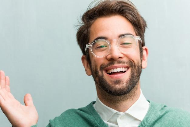 Die junge hübsche unternehmermann-gesichtsnahaufnahme, die spaß lacht und hat, entspannt und nett ist, fühlt sich überzeugt und erfolgreich