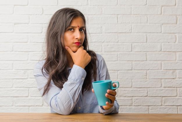 Die junge indische frau, die oben denkt und über eine idee verwirrt nachdenkt, würde versuchen, eine lösung zu finden