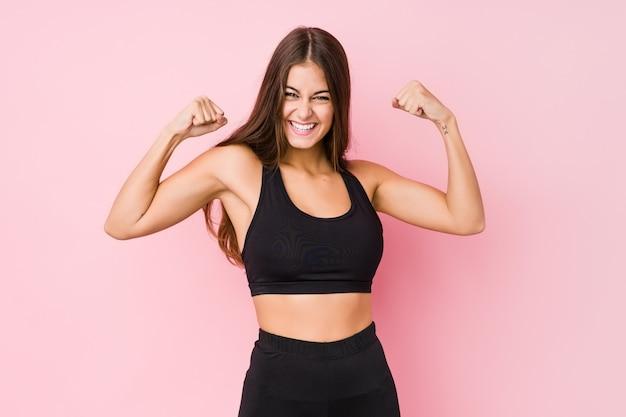 Die junge kaukasische eignungsfrau, die sport tut, lokalisierte das zeigen der stärkegeste mit den armen, symbol der weiblichen energie