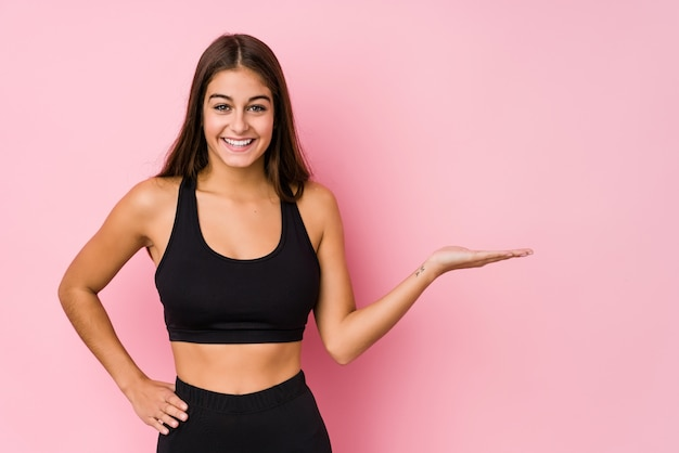 Die junge kaukasische eignungsfrau, die sport tut, lokalisierte das zeigen eines kopienraumes auf einer palme und das halten einer anderen hand auf taille.