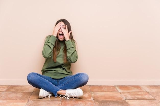 Die junge kaukasische frau, die auf dem fußboden sitzt, lokalisierte blinzeln durch die finger, die erschrocken und nervös sind.