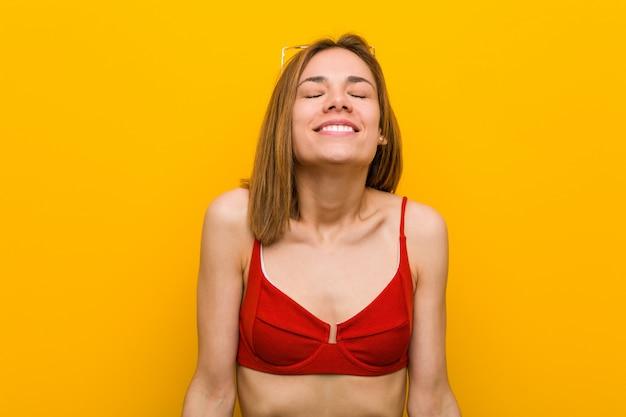 Die junge kaukasische frau, die bikini und sonnenbrille trägt, lacht und schließt augen, fühlt sich entspannt und glücklich.