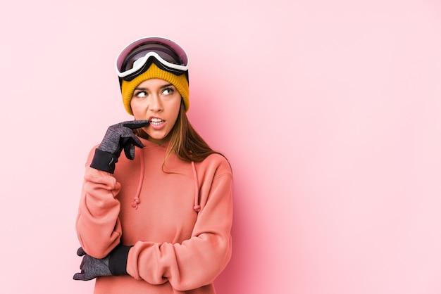 Die junge kaukasische frau, die eine skikleidung trägt, isolierte entspanntes denken über etwas, das einen kopienraum betrachtet.