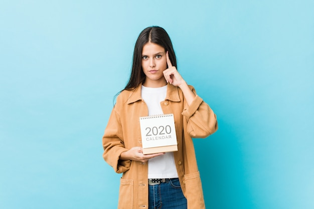 Die junge kaukasische frau, die einen kalender 2020s zeigt seinen tempel mit dem finger hält und denkt, konzentrierte sich auf eine aufgabe.