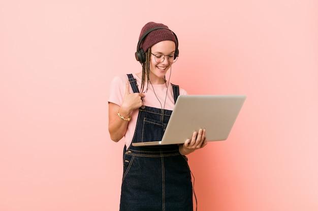 Die junge kaukasische frau, die einen laptop anhält, überraschte das zeigen auf und breit lächelte.