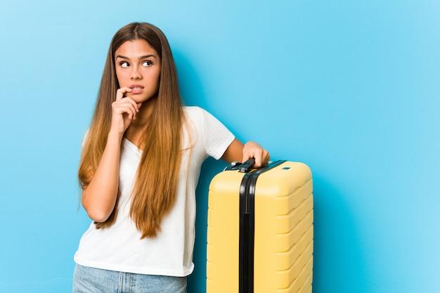Die junge kaukasische frau, die einen reisekoffer hält, entspannte sich das denken an etwas