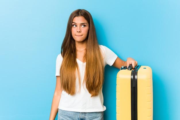 Die junge kaukasische frau, die einen reisekoffer verwirrt hält, fühlt sich zweifelhaft und unsicher.