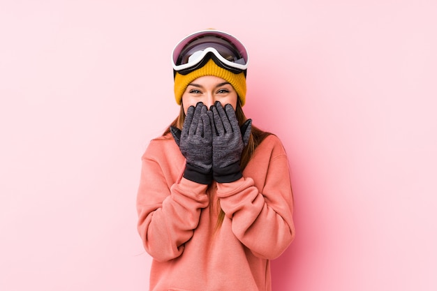 Die junge kaukasische frau, die einen ski trägt, kleidet das getrennte lachen über etwas und bedeckt mund mit den händen.