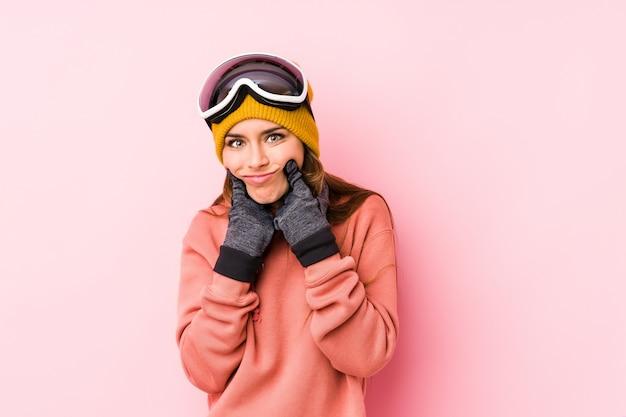 Die junge kaukasische frau, die einen ski trägt, kleidet das getrennte zweifeln zwischen zwei wahlen.
