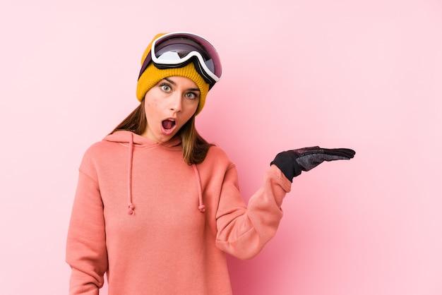Die junge kaukasische frau, die einen ski trägt, kleidet das lokalisierte beeindruckte halten des kopienraumes auf palme.