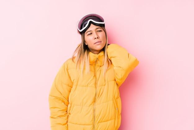 Die junge kaukasische frau, die einen ski trägt, kleidet in einem leidenden nackenschmerzen des rosa hintergrundes wegen des sitzenden lebensstils.