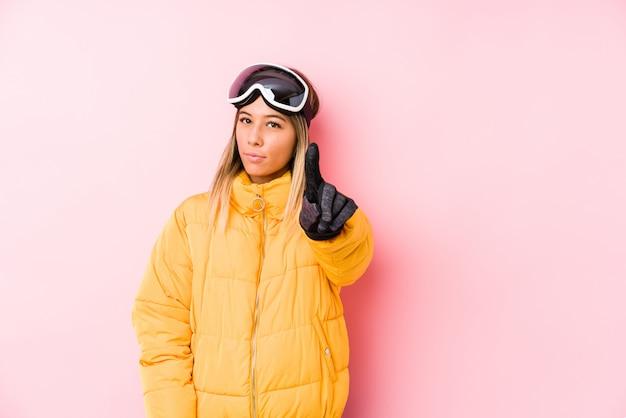 Die junge kaukasische frau, die einen ski trägt, kleidet in einem rosa hintergrund, der nummer eins mit dem finger zeigt.