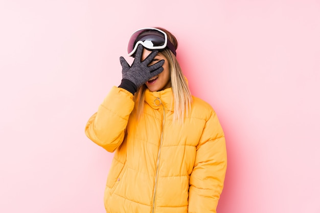 Die junge kaukasische frau, die einen ski trägt, kleidet in einem rosa wandblinzeln an durch finger, verlegenes bedeckungsgesicht.