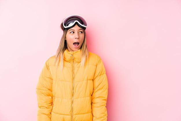Die junge kaukasische frau, die einen ski trägt, kleidet in einer rosa wand, die wegen etwas entsetzt wird, das sie gesehen hat.