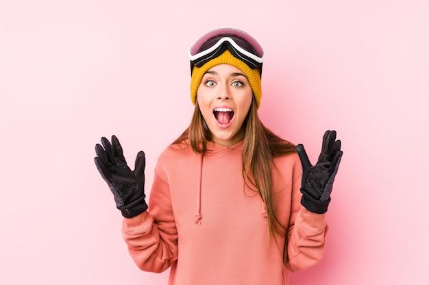 Die junge kaukasische frau, die einen ski trägt, kleidet lokalisiertes empfangen einer angenehmen überraschung, aufgeregt und hände anhebend.
