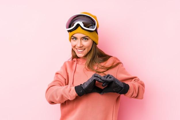 Die junge kaukasische frau, die einen ski trägt, kleidet lokalisiertes lächeln und das zeigen einer herzform mit den händen.
