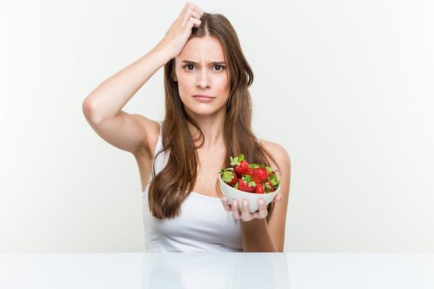 Die junge kaukasische frau, die erdbeerschüssel entsetzt hält, hat sie sich an wichtige sitzung erinnert.