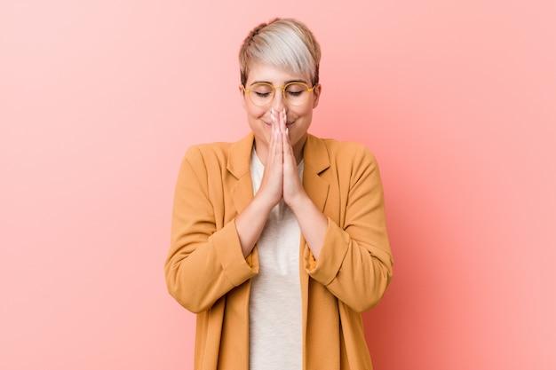Die junge kaukasische frau, die händchenhalten einer zufälligen geschäftskleidung trägt, beten herein nahe mund, fühlt sich überzeugt.