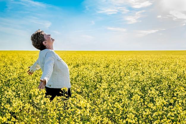 Die junge kaukasische frau, die mit den armen steht, hob auf einem canolagebiet in der blüte an