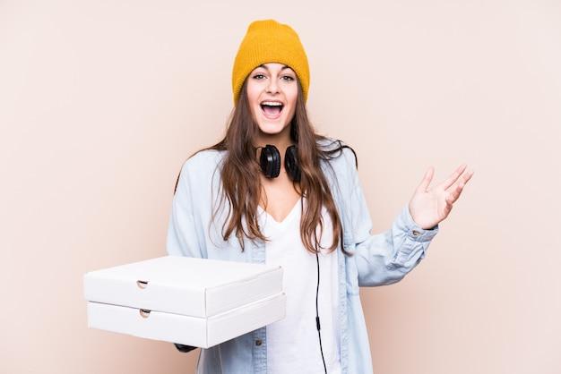 Die junge kaukasische frau, die pizzas hält, lokalisierte das empfangen einer angenehmen überraschung, aufgeregt und hände anhebend.