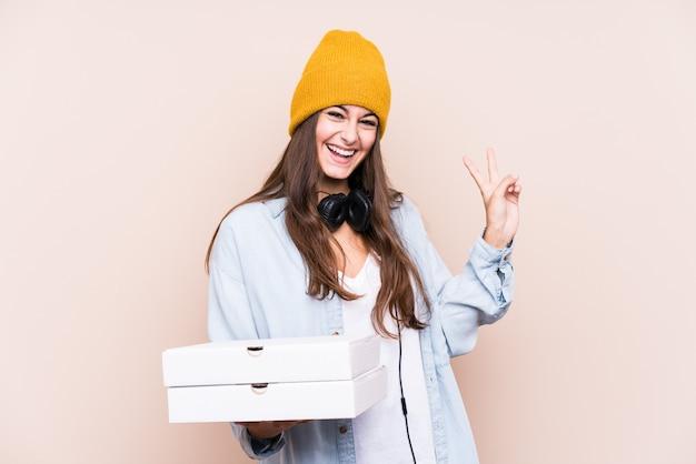 Die junge kaukasische frau, die pizzas hält, lokalisierte das frohe und sorglose zeigen eines friedenssymbols mit den fingern.