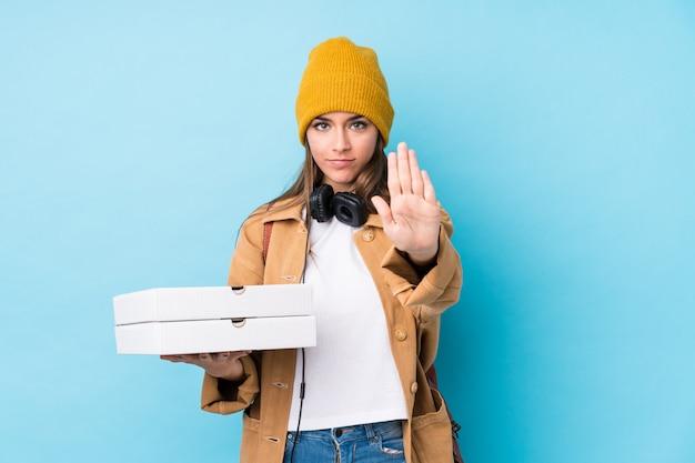 Die junge kaukasische frau, die pizzas hält, lokalisierte stellung mit der ausgestreckten hand, die das stoppschild zeigt und verhinderte sie.