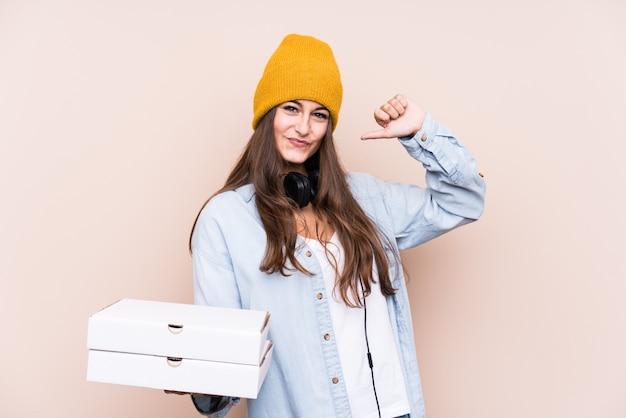 Die junge kaukasische frau, die pizzas lokalisiert hält, fühlt sich stolz und selbstbewusst, beispiel zu folgen.