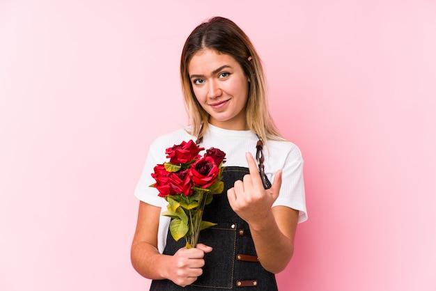 Die junge kaukasische frau, die rosen hält, lokalisierte das zeigen mit dem finger auf sie, als ob einladung näher kommen.