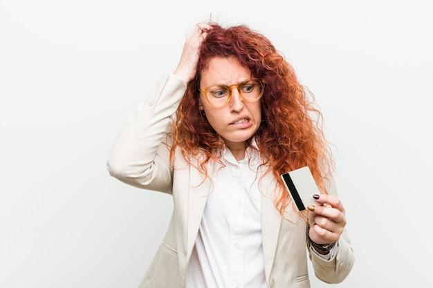 Die junge kaukasische rothaarigefrau, die eine kreditkarte entsetzt hält, hat sich an wichtige sitzung erinnert.