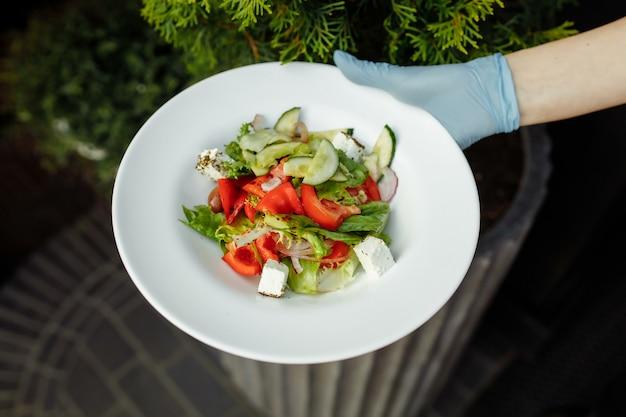 Die junge kellnerin hält den teller mit dem griechischen salat in den händen