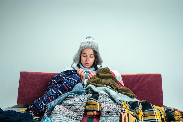 Die junge kranke frau mit rauchabzug sitzt auf dem sofa zu hause oder im studio, bedeckt mit gestrickter warmer kleidung. krankheit, influenza, schmerzkonzept. entspannung zu hause. gesundheitskonzepte.