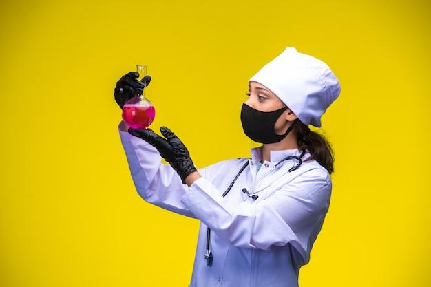 Die junge krankenschwester in gesichts- und handmaske hält den chemiekolben darüber und überprüft ihn.