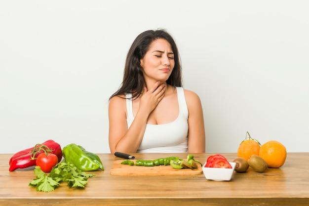 Die junge kurvige frau, die eine gesunde mahlzeit zubereitet, leidet die schmerz in der kehle wegen eines virus oder einer infektion.