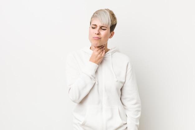 Die junge kurvige frau, die einen weißen hoodie trägt, erleidet die schmerz in der kehle wegen eines virus oder einer infektion.