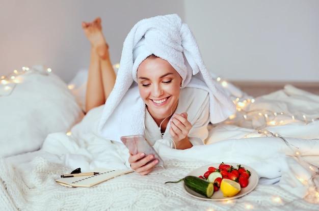 Die junge lächelnde frau, die ihren badekurortmorgen genießt und wachen auf.
