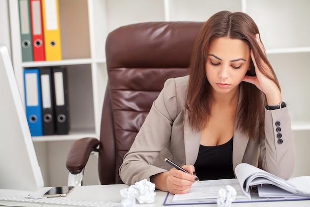 Die junge langweilige geschäftsfrau, die am tisch mit laptop sitzt und möchten schlafen, während am arbeitsplatz im modernen büro gähnen.