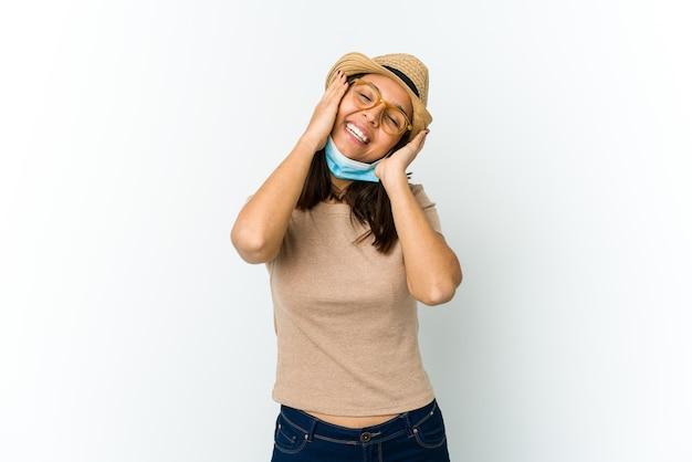 Die junge lateinamerikanische frau, die hut und maske trägt, um vor der auf der weißen wand isolierten decke zu schützen, lacht freudig und hält die hände auf dem kopf. glückskonzept.