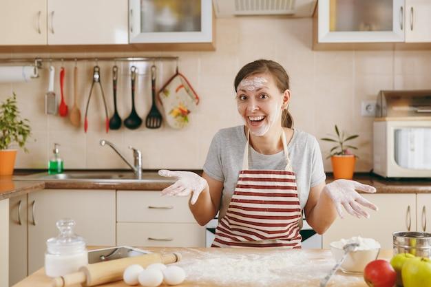 Die junge lustige fröhliche frau sitzt an einem tisch mit mehl und bereitet einen kuchen in der küche zu. kochen nach hause. essen zubereiten.