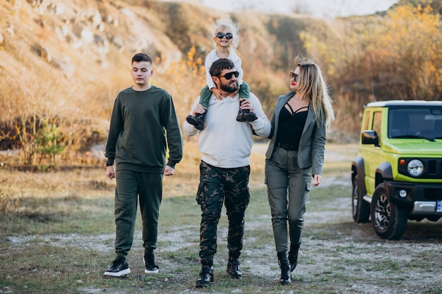 Die junge moderne familie, die mit dem auto reist und hielt für einen spaziergang im park an
