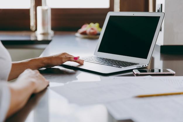 Die junge moderne geschäftsfrau, die zu hause mit dokumenten und laptop arbeitet