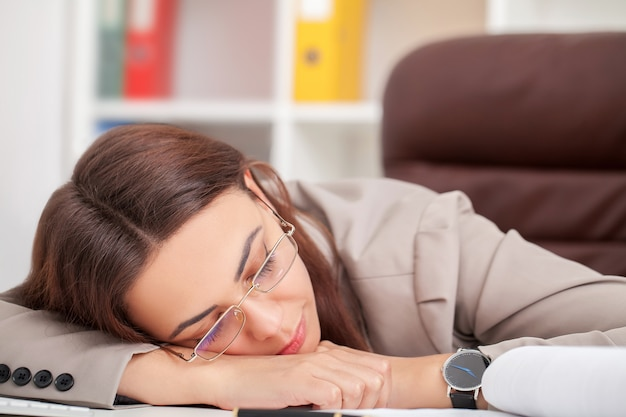Die junge müde frau am schreibtisch schlafend mit augen schloss