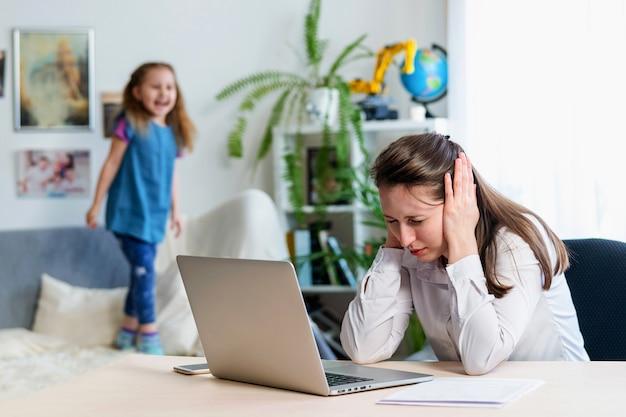 Die junge mutter arbeitet zu hause mit einem laptop zusammen mit einer kleinen tochter.
